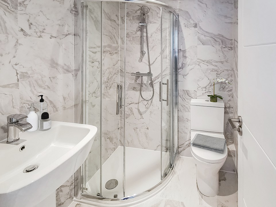 Inside the building is a stunning bathroom complete with a beautiful marble tile floor, a large curved glass shower and a heated towel rail